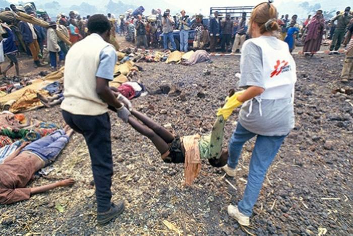 1994年,志愿者从难民营中抬出死亡难民的尸体。
