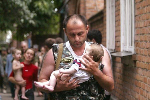 俄罗斯也成为恐怖分子袭击的目标。图片显示的是2004年9月2日,一位警官在北奥赛梯抱着一名无辜的婴儿。